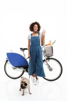 Ritratto di donna adorabile che mostra segno ok mentre si trova in piedi con il suo carlino e la bicicletta isolati su un muro bianco