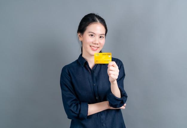 Ritratto di una giovane donna asiatica adorabile che mostra la carta di credito