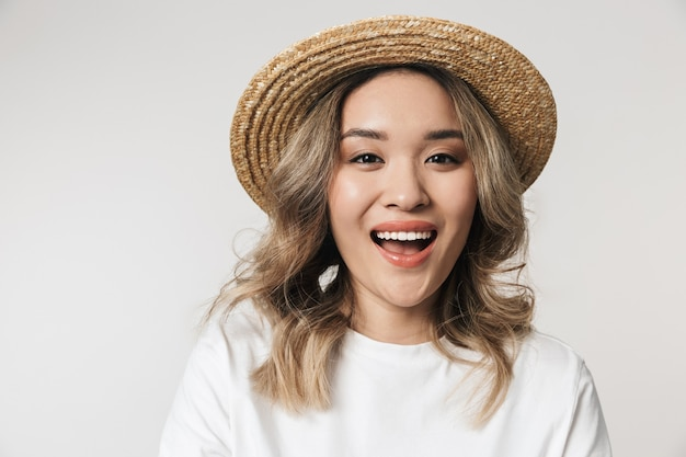 Ritratto di una giovane donna asiatica adorabile in piedi isolata su un muro bianco, con indosso un cappello estivo, in posa