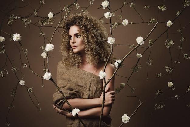 Ritratto di bella giovane donna con acconciatura afro e bellissimo trucco con molti fiori bianchi sul muro