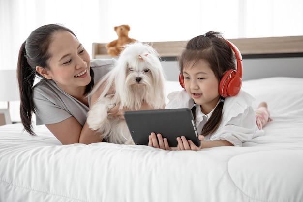 Ritratto di famiglia amorevole con tempo libero cane barboncino bianco e musica d'ascolto sul letto in camera da letto.