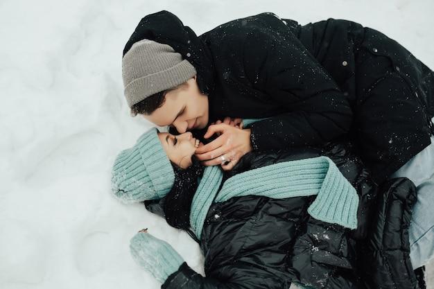 Ritratto di coppia di innamorati sono sdraiati sulla neve in inverno nella foresta.