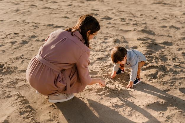 Ritratto di madre amorevole e suo figlio di un anno che cammina e gioca con la sabbia.