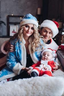 Ritratto di genitori amorevoli in costumi tradizionali di snow maide e father frost con la piccola santa.