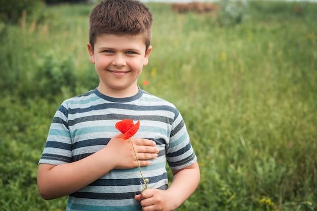 Ritratto di un ragazzo dolce e fortunato con un fiore di papavero rosso il bambino preme un fiore di campo al suo cuore