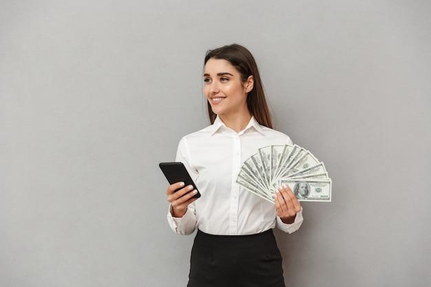 Ritratto di fortunata giovane donna 20s in bianco e nero indossare sorridente mentre si tiene la ventola di soldi e telefono cellulare in mano, isolato sopra il muro grigio