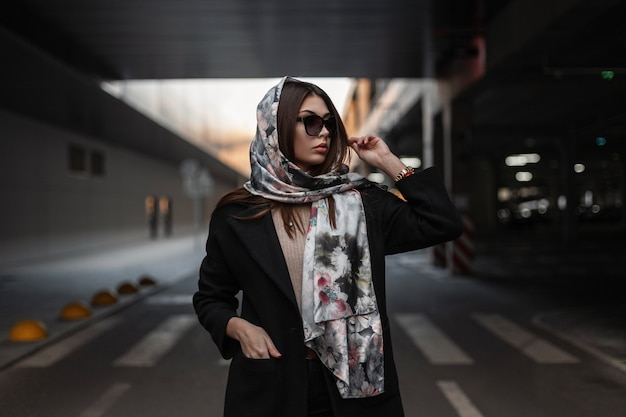 Ritratto di giovane donna lussuosa in eleganti occhiali da sole scuri con labbra sexy in sciarpa vintage di seta in cappotto nero in città sulla strada. modello grazioso americano della ragazza di affari all'aperto. signora alla moda.