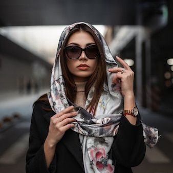 Ritratto di giovane donna lussuosa in eleganti occhiali da sole scuri con labbra sexy in una sciarpa vintage di seta in cappotto nero in città sulla strada. modello grazioso attraente della ragazza di affari all'aperto. signora alla moda