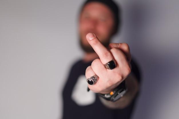 Ritratto di un uomo arrabbiato pazzo che mostra vaffanculo gesto e guardando la telecamera isolata su sfondo bianco