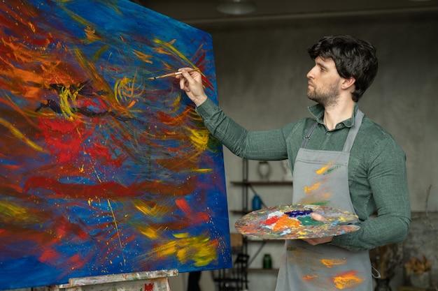Ritratto dell'artista maschio che lavora alla pittura nell'artista maschio dello studio fa i colpi con vernice gialla