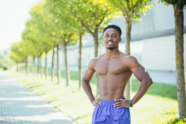 Il ritratto di un atleta maschio che guarda nell'obiettivo motiva l'allenatore a condurre uno stile di vita attivo