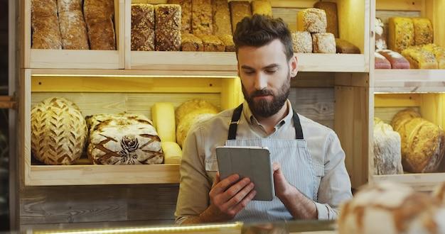 Ritratto del panettiere maschio che lavora nel negozio del forno e che utilizza compressa