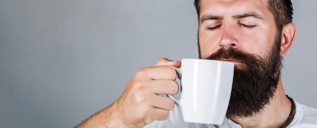 Ritratto maschile. tè del primo piano. buongiorno, uomo che tiene una tazza di tè. concetto di mattina. il maschio barbuto bello tiene la tazza di caffè, tè. uomo sorridente dei pantaloni a vita bassa con la tazza di caffè fresco.
