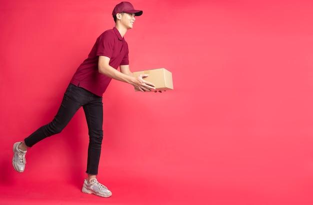 Ritratto di un uomo di consegna maschio che tiene una scatola di carico, sfondo