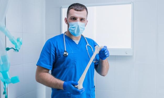 Ritratto di un medico di sesso maschile sullo sfondo di un negatoscopio con un osso in mano. radiologia. concetto medico. tecnica mista