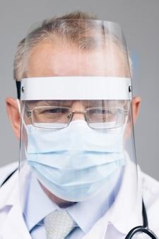 Ritratto di medico maschio con gli occhiali che indossa una maschera protettiva trasparente per il viso e una tuta in una stanza d'ospedale al covid19