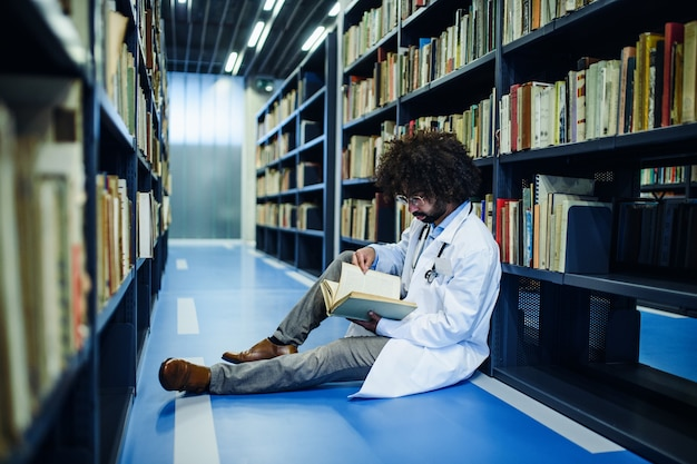 Ritratto di medico maschio seduto in biblioteca, studiando informazioni sul virus corona.
