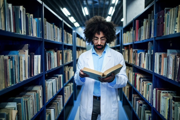 Ritratto di medico maschio in piedi in biblioteca, studiando informazioni sul virus corona.