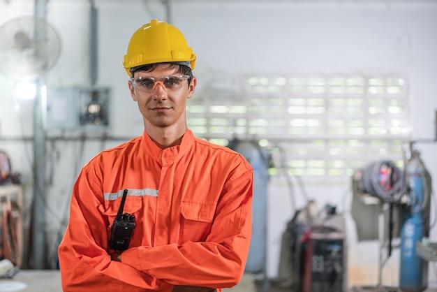Ritratto di ingegnere maschio in arancione uiform bracci trasversali in piedi in fabbrica industrial