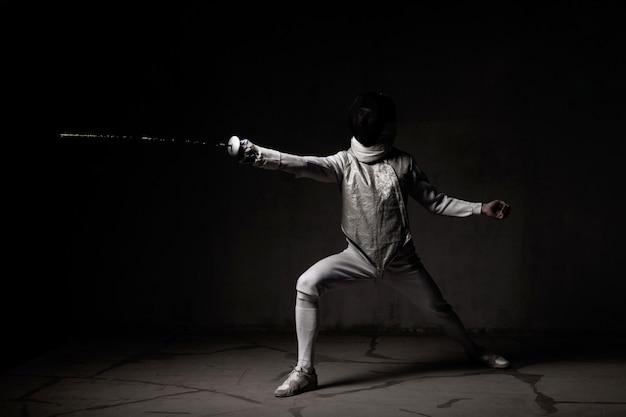 Ritratto dello schermitore maschio nella maschera e nella stagnola che eseguono lotta
