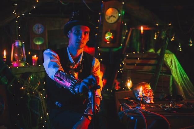 Ritratto di inventore maschio in un abito steampunk, un cappello a cilindro con un bastone in mano si trova in un laboratorio di orologi con luce al neon. cosplay cyberpunk