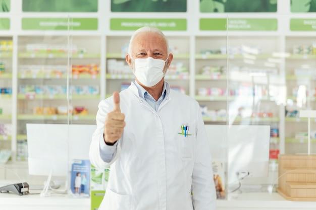 Ritratto di un farmacista maschio che mostra un segno di approvazione con la mano