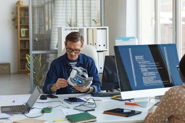 Ritratto di un ingegnere informatico maschio che tiene in mano un auricolare vr mentre lavora su applicazioni di realtà aumentata, spazio di copia