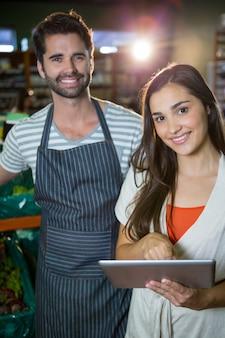 Ritratto del personale maschile che sta con una donna che per mezzo della compressa digitale