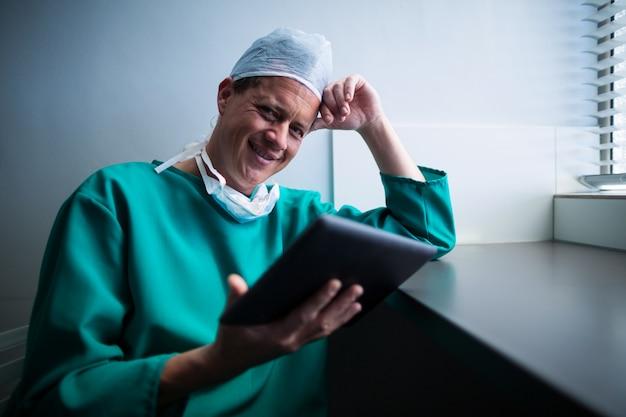 Ritratto del chirurgo maschio che per mezzo della compressa digitale