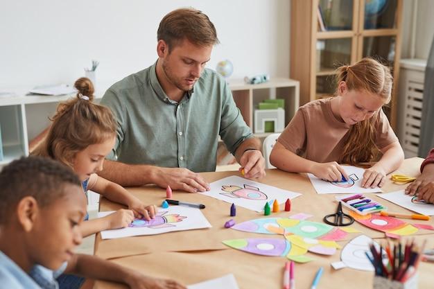 Ritratto di insegnante maschio che lavora con un gruppo multietnico di bambini che disegnano immagini durante la lezione d'arte nella scuola o nel centro di sviluppo