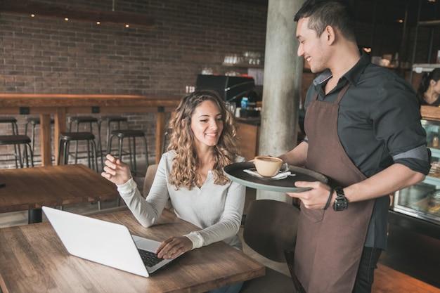 Ritratto di una cameriera maschio che serve caffè a un cliente di sesso femminile