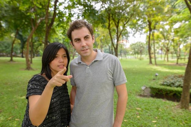 Ritratto di uomo e donna asiatica come coppia multietnica insieme e innamorato al parco all'aperto