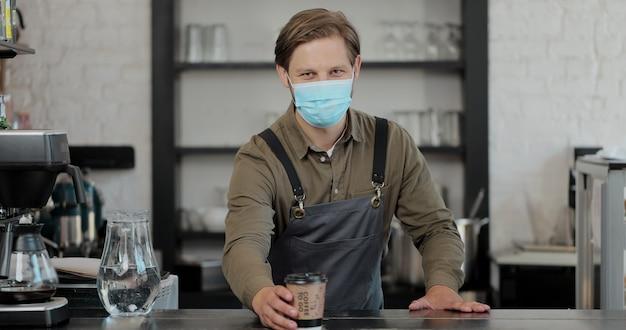 Ritratto di uomo barista in maschera medica cameriera che tiene tazza di caffè sentirsi felice al caffè urbano. concetto di caffetteria.