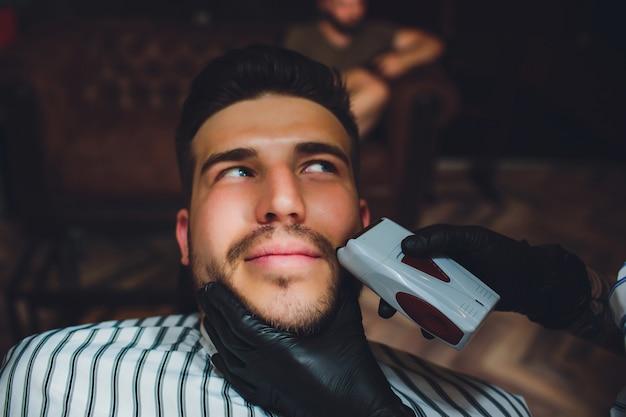 Ritratto di barba uomo nel negozio di barbiere. mano femminile.