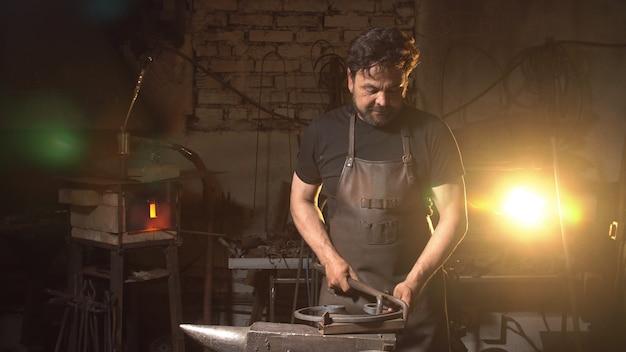 Ritratto di un uomo di un fabbro nell'atmosfera di lavoro.