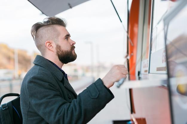 Ritratto di un uomo che sceglie il fast food in un camion di cibo nell'industria alimentare dei pasti di strada e nel cibo di strada