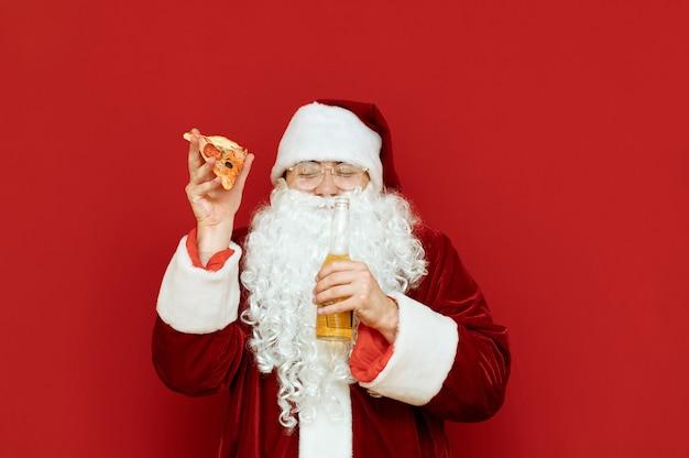 Ritratto di uomo vestito da babbo natale che tiene una bottiglia di birra e un trancio di pizza