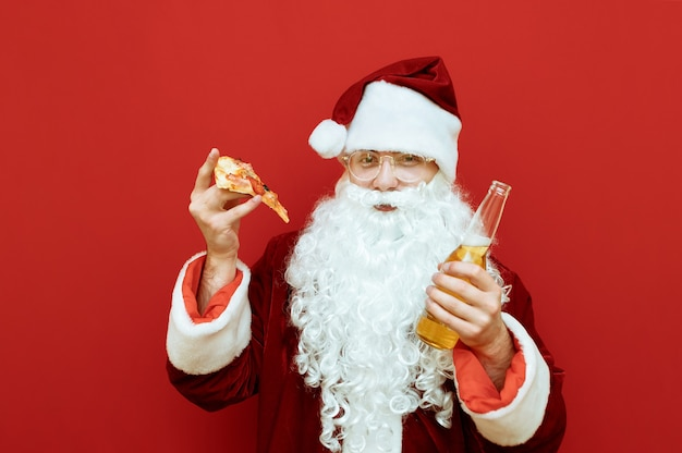 Uomo ritratto vestito da babbo natale tenendo la pizza e la birra