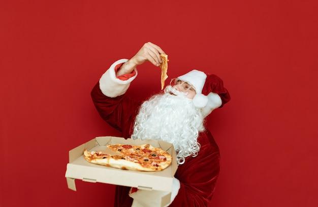 Ritratto uomo vestito da babbo natale tenendo la pizza