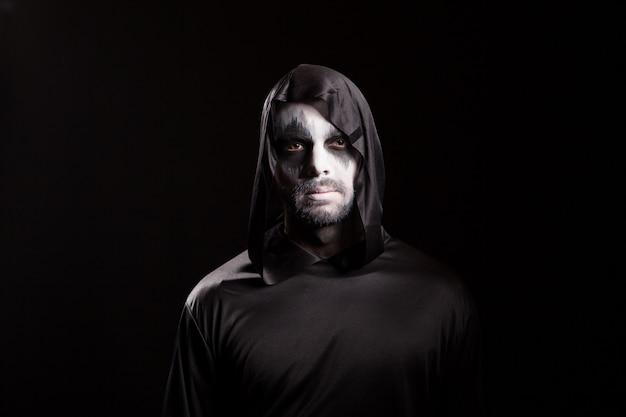 Ritratto di uomo vestito come angelo della morte su sfondo nero per halloween.