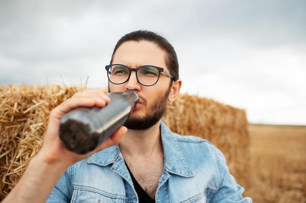 Ritratto di uomo che beve acqua da termo bottiglia in acciaio vicino a mucchi di fieno.