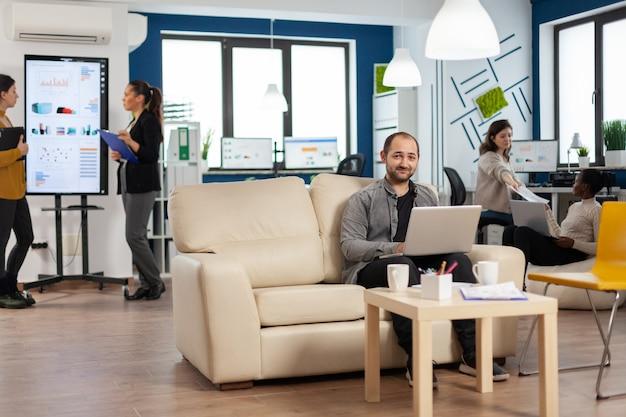 Ritratto dell'impiegato dell'uomo che scrive sul computer portatile che esamina sorridere della macchina fotografica