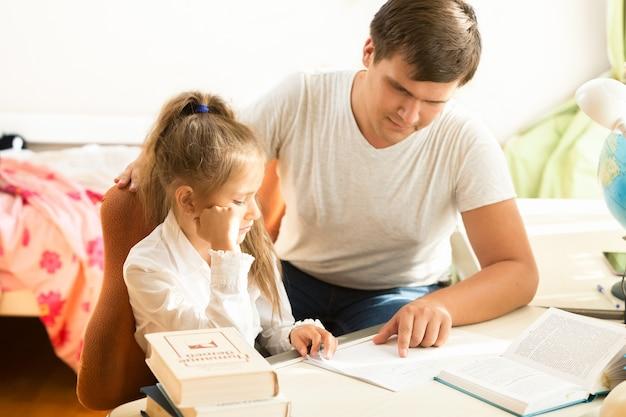 Ritratto di uomo che spiega alla figlia come fare i compiti