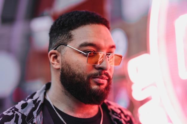 Ritratto di un uomo con gli occhiali con luci al neon. foto di alta qualità