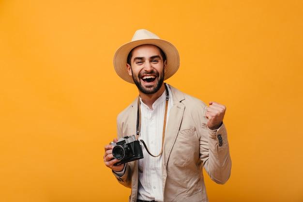 Ritratto di uomo di buon umore in posa con fotocamera retrò