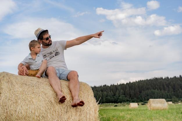 Ritratto dell'uomo e del suo figlioletto seduti su un pagliaio rotondo in un campo verde nella soleggiata giornata estiva summer