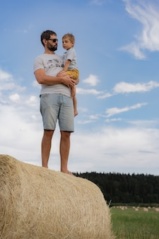 Ritratto dell'uomo e del suo figlioletto in piedi su un pagliaio rotondo in un campo verde nella soleggiata giornata estiva summer