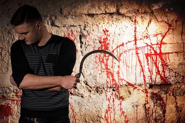 Ritratto di un uomo che tiene una lama in piedi vicino a un muro macchiato di sangue per il concetto di omicidio e spaventose vacanze di halloween