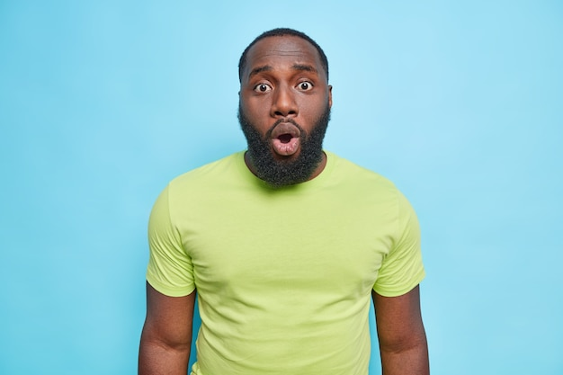Il ritratto dell'uomo sembra imbarazzato davanti ha un'espressione scioccata tiene la bocca aperta indossa una maglietta verde casual isolata sul muro blu