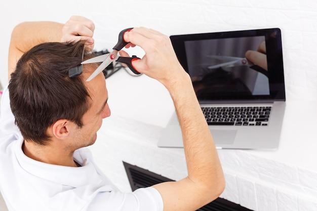Ritratto di un uomo che si taglia i capelli durante la quarantena